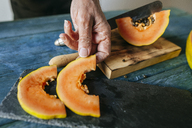 Close-up of man's hands placing pieces of papaya on slate plate - KIJF01825