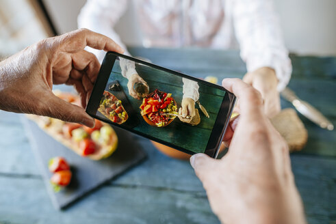 Close-up of man's hands taking a picture with mobile phone eating salad of tomato, pomegranate, papaya and olives, with papaya with fruits on the side and with glass of wine - KIJF01834