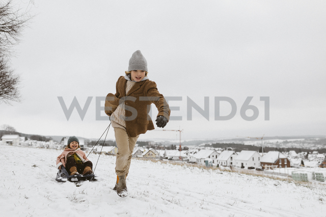 Boy pulling sledge with little sister in snow - KMKF00109