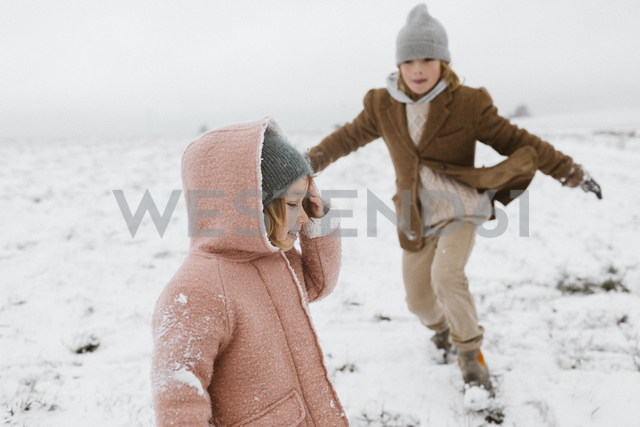 Happy little girl in the snow with brother playing in the background - KMKF00112