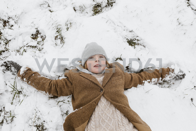 Portrait of boy lying on snow-covered meadow making a snow angel - KMKF00115