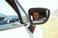 Reflection of young woman in wing mirror of a car - SRYF00697