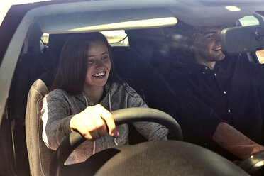 Happy young woman with boyfriend driving car - SRYF00700