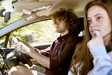Young man with girlfriend driving car - SRYF00703