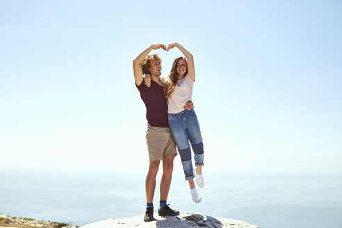 South Africa, Cape Town, happy young couple on top of a mountain at the coast - SRYF00706
