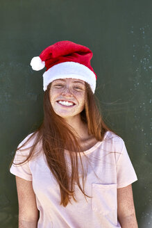 Portrait of smiling young woman wearing Christmas hat - SRYF00709