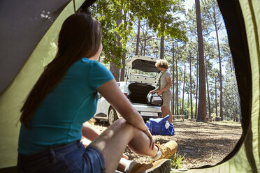 Young woman sitting in a tent watching her boyfriend packing the car - SRYF00715