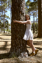 Smiling young woman hugging a tree in forest - SRYF00721