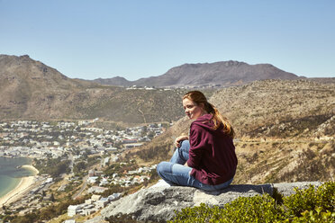 South Africa, Cape Town, young woman sitting at the coast looking at view - SRYF00730