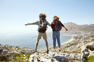 South Africa, Cape Town, young couple jumping on a trip at the coast - SRYF00733