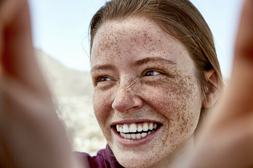 Portrait of laughing young woman with freckles outdoors - SRYF00736