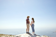 South Africa, Cape Town, young couple standing on top of a mountain at the coast - SRYF00742