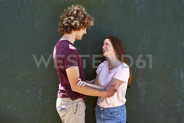 Smiling young couple in front of a green wall - SRYF00760