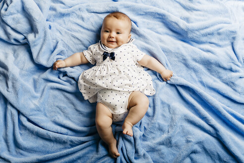 Portrait of smiling baby girl lying on light blue blanket - JRFF01490