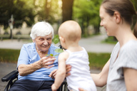 Portrait of happy senior woman with daughter and granddaughter in a park - DIGF03208