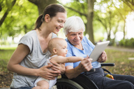 Grandmother, daughter and granddaughter having fun with tablet in a park - DIGF03211