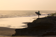 Indonesia, Bali, young woman with surfboard, looking at distance - KNTF00949