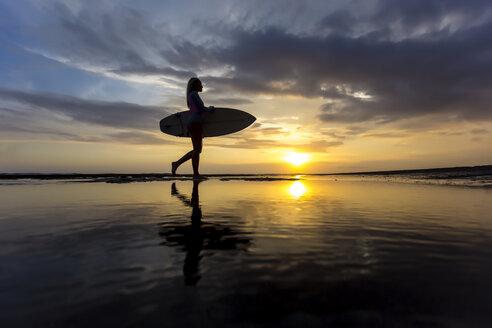 Indonesia, Bali, young woman with surfboard at sunset - KNTF00952