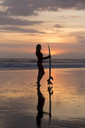 Indonesia, Bali, young woman with surfboard at sunset - KNTF00955