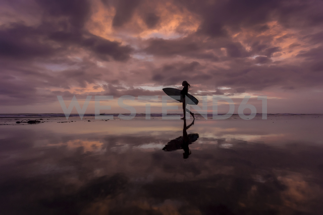 Indonesia, Bali, young woman with surfboard in the evening - KNTF00958