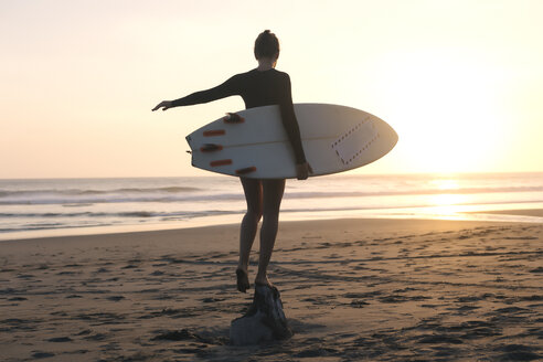 Indonesia, Bali, young woman with surfboard standing on stone at sunset - KNTF00964