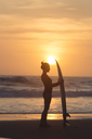 Indonesia, Bali, young woman with surfboard at sunset - KNTF00967