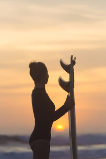 Indonesia, Bali, young woman with surfboard - KNTF00970