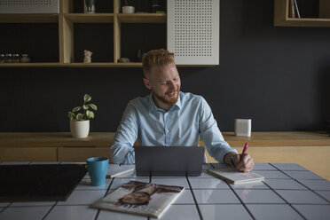 Smiling businessman with laptop and notebook working at home - MOMF00345