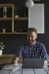 Smiling man using credit card and laptop at home - MOMF00354