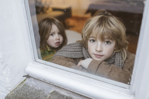Portrait of boy looking out of window with his little sister in the background - KMKF00123