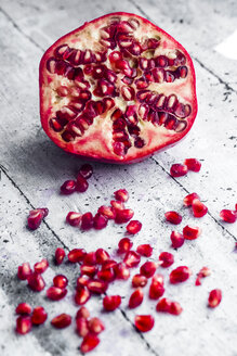Sliced pomegranate and pomegranate seed on wood - SARF03454