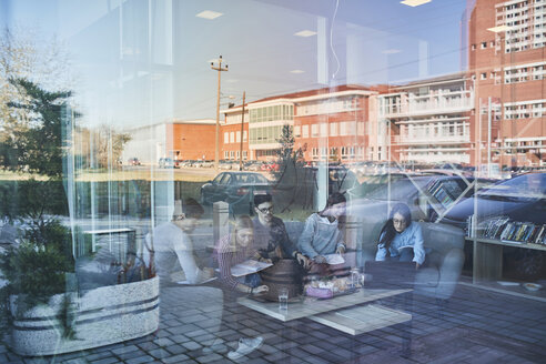 Group of friends sitting together in a cafe with reflection of glass pane - ZEDF01041