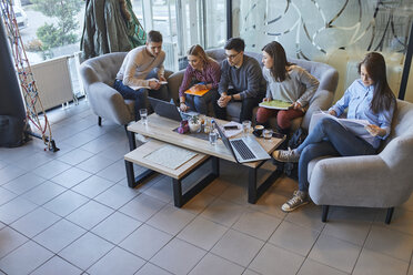 Group of friends sitting together in a cafe with laptop and documents - ZEDF01044