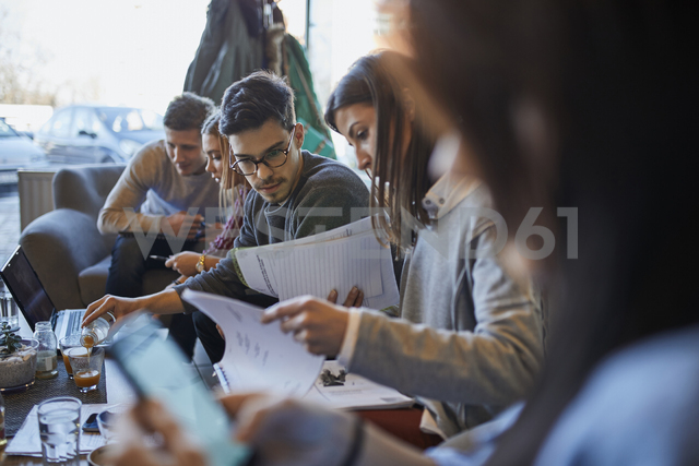 Group of friends sitting together in a cafe with laptop and documents - ZEDF01050 - Zeljko Dangubic/Westend61