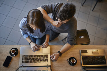Top view of young woman and man in a cafe sharing a laptop - ZEDF01071