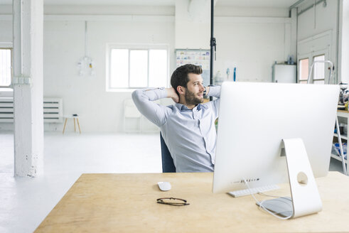 Smiling businessman sitting at desk in office having a break - MOEF00636