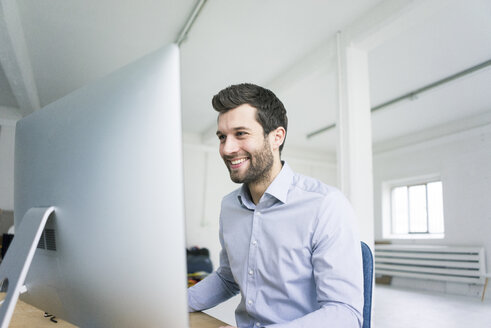 Smiling businessman working at desk in office - MOEF00639
