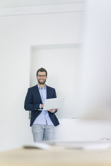 Portrait of smiling businessman with laptop in office - MOEF00642