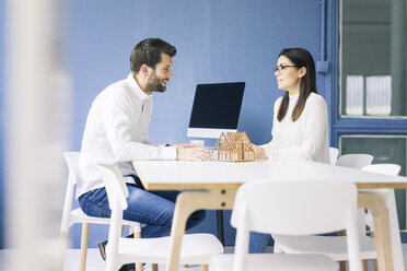 Man and woman talking with architectural model on table - MOEF00648