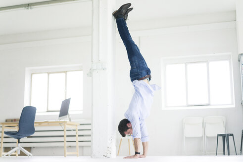 Businessman doing a handstand in office - MOEF00651