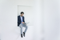 Businessman sitting in a niche using laptop - MOEF00663