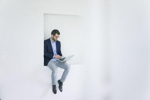 Businessman sitting in a niche using laptop - MOEF00663