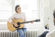 Woman playing guitar for man - MOEF00675