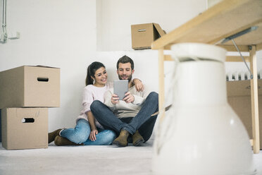 Couple sitting in new home surrounded by cardboard boxes looking at tablet - MOEF00681
