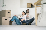Laughing couple sitting in new home surrounded by cardboard boxes - MOEF00684