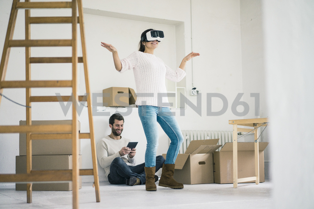 Couple in new home with woman wearing VR glasses - MOEF00687