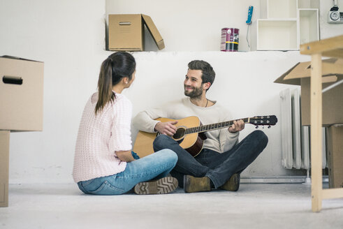 Couple sitting on the floor in new home playing guitar - MOEF00690