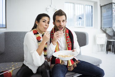 German football fan couple sitting on couch eating chips and watching Tv - MOEF00699
