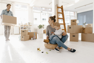 Family moving into new home with father carrying cardboard box - KNSF03389