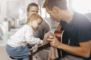 Little girl examining father's guitar at home - KNSF03407
